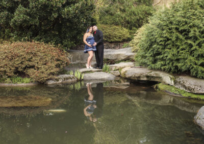 Couple with baby on the way by a pond.